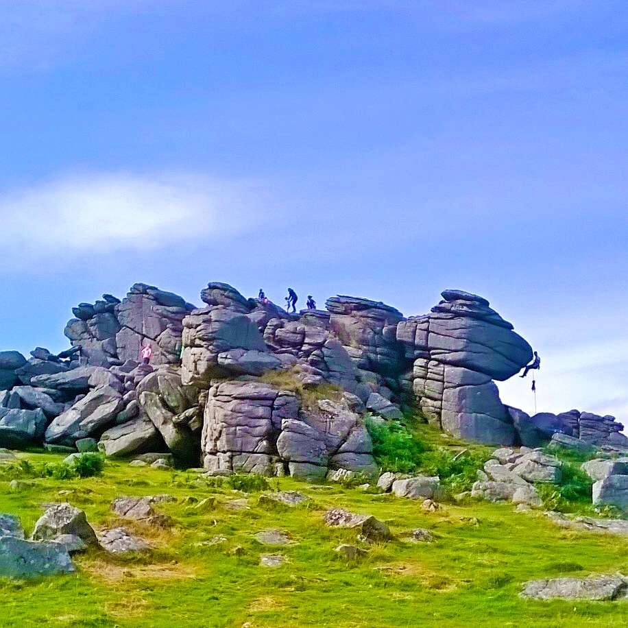A view of Houndtor with a climber scaling the tor