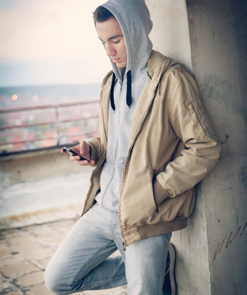 A teenager using his mobile phone